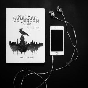 Buch Narrenlauf mit Handy und Kopfhörern daneben