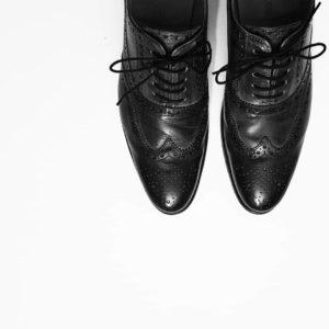 Schwarzweißbild, ein paar schicke Herrenschuhe aus Leder vor weißem Hintergrund